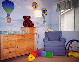 Baby's Nursery - The mural in this baby boy's nursery features hot air balloons filled with a variety of friendly animals. The custom swivel rocker creates a great spot to nurse or just sit and cuddle. The stuffed animals and the whimsical floor lamp complete the design.
