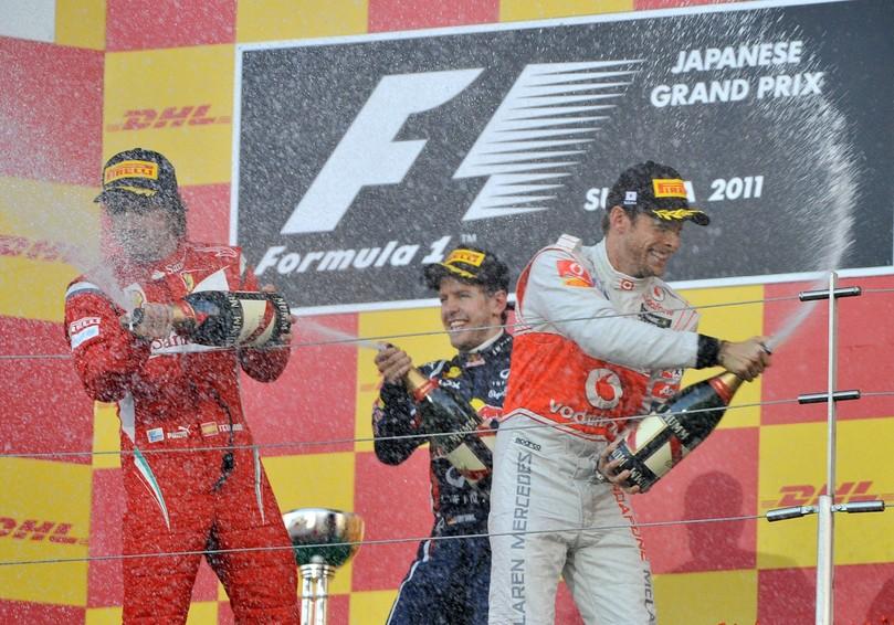 Фернандо Алонсо Себастьян Феттель Дженсон Баттон расплескивают шампанское на подиуме Сузуки на Гран-при Японии 2011
