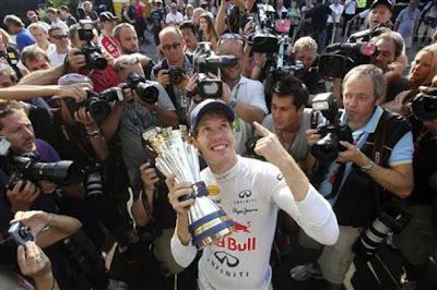 Себастьян Феттель с трофеем в руках показывает палец на Гран-при Италии 2011 в Монце