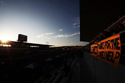 плакат болельщиков Льюиса Хэмилтона под заходящим солнцем трассы Сузука на Гран-при Японии 2011
