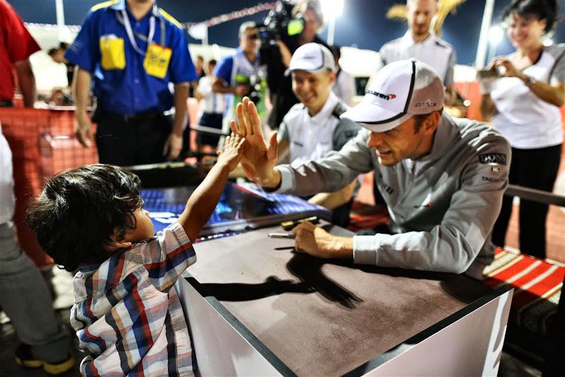 Дженсон Баттон дает пять маленькому болельщу на автограф-сессии Гран-при Бахрейна 2014