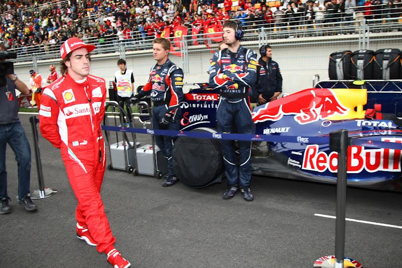 Фернандо Алонсо проходит мимо болида Red Bull на стартовой решетке Гран-при Кореи 2011