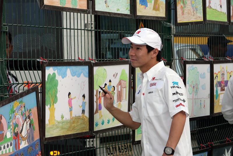 Камуи Кобаяши подписывает картины на Гран-при Индии 2011