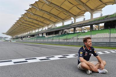 Себастьян Феттель сидит на старт-финишной черте трассы Куала-Лумпур на Гран-при Малайзии 2013
