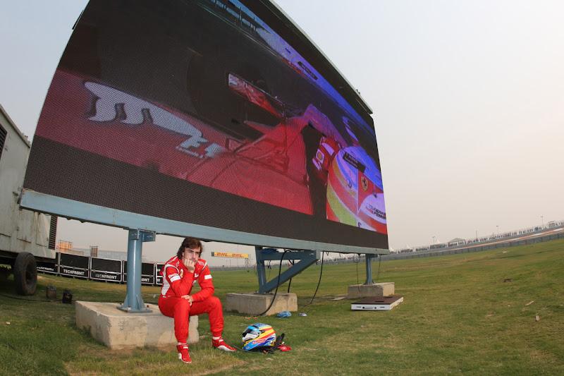 Фернандо Алонсо сидит под экраном на трассе Буддх после своего схода во время второй сессии свободных заездов на Гран-при Индии 2011