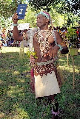 Miniafia man holding New Testament