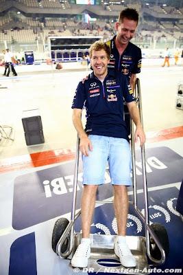 механик Red Bull катает Себастьяна Феттеля на тележке на Гран-при Абу-Даби 2014