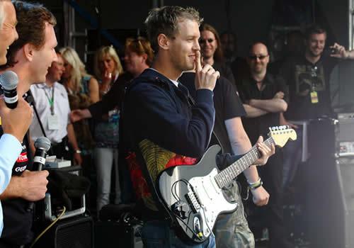 Себастьян Феттель с гитарой на фестивале после Гран-при Великобритании 2011 в Сильверстоуне