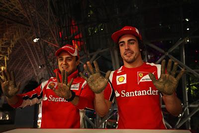 Фелипе Масса и Фернандо Алонсо показывают руки после отпечаток рук в Ferrari World на Гран-при Абу-Даби 2011