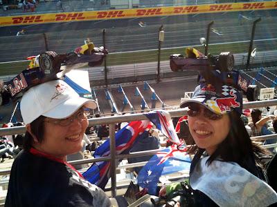 болельщиы Red Bull в кепках с болидами на трибунах Сузуки на Гран-при Японии 2011