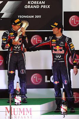 Себастьян Феттель с трофеем и Марк Уэббер вытирает руку об напарника на подиуме Гран-при Кореи 2011