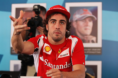 недоумевающий Фернандо Алонсо протягивает руку на автограф-сессии Яс Марины на Гран-при Абу-Даби 2011
