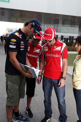 Марк Уэббер показывает книжку Фелипе Массе и Фернандо Алонсо на Гран-при Индии 2011