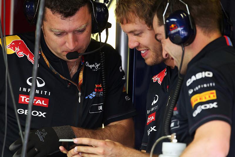 Себастьян Феттель показывает что-то на телефоне механикам на Гран-при Италии 2011