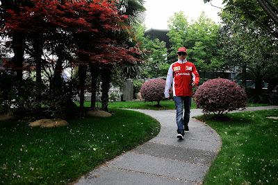 Кими Райкконен идет по зеленому паддоку Шанхая на Гран-при Китая 2014