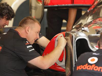 механик McLaren рисует на болиде Льюиса на Гран-при Абу-Даби 2011