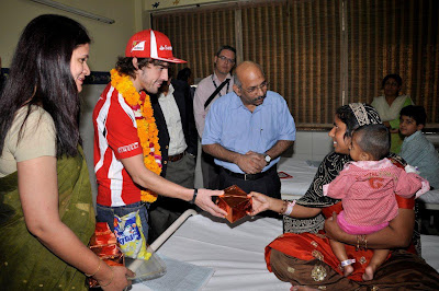 Фернандо Алонсо передает подарок индийской семье на Гран-при Индии 2011
