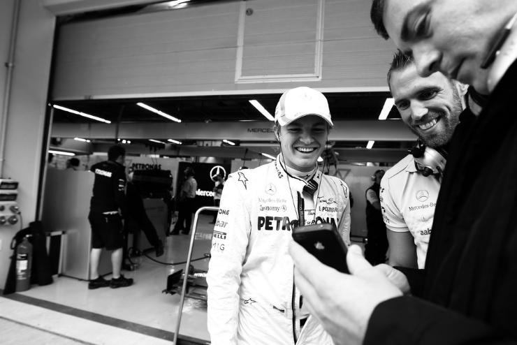 механики показывают что-то смешное на телефоне Нико Росбергу на Гран-при Кореи 2011