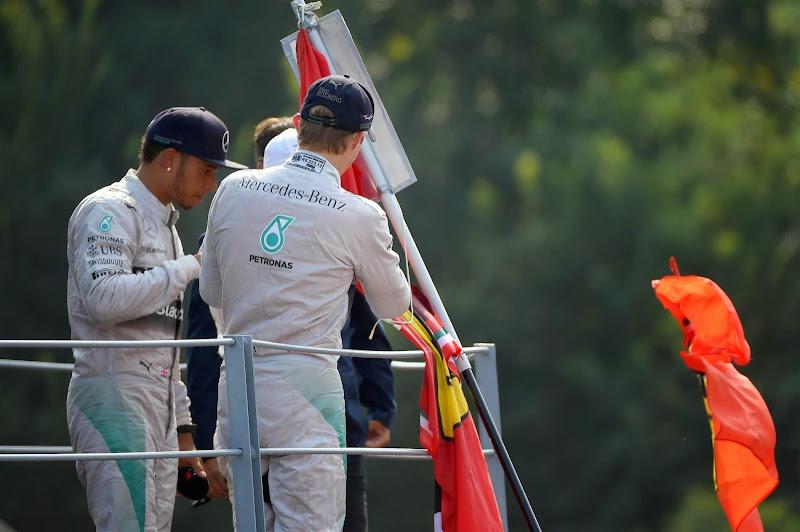 Нико Росберг ставит автограф на флаге болельщика на подиуме Монцы на Гран-при Италии 2014