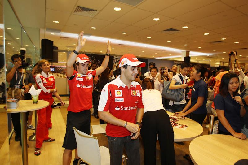 Фернандо Алонсо с поднятыми руками позади Фелипе Массы на Гран-при Сингапура 2010