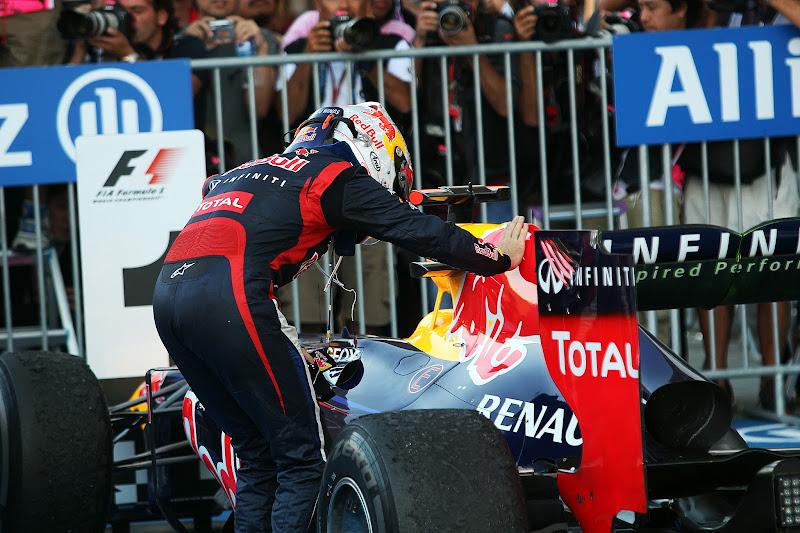 Себастьян Феттель гладит свой болид Red Bull после победы на Сузуке на Гран-при Японии 2012