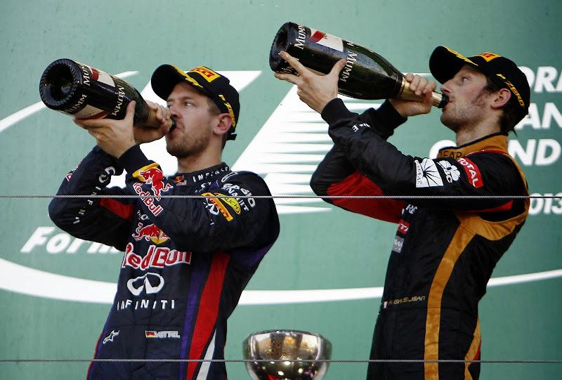 Себастьян Феттель и Ромэн Грожан синхронно пьют шампанское на подиуме Гран-при Японии 2013