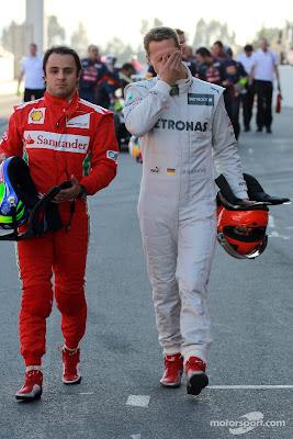 Фелипе Масса и фэйспалмящий Михаэль Шумахер идут по пит-лейну на предсезонных тестах 2012 в Барселоне 23 февраля 2012