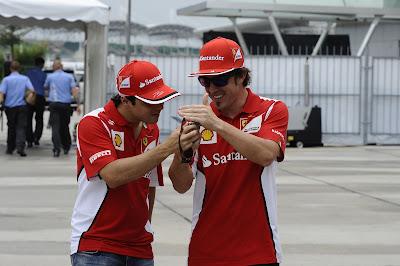 Фернандо Алонсо показывает что-то забавное на телефоне Фелипе Массе на Гран-при Малайзии 2012