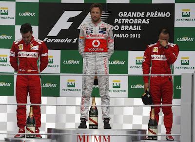Дженсон Баттон в окружении пилотов Ferrari Фернандо Алонсо и Фелипе Массы на подиуме Интерлагоса на Гран-при Бразилии 2012