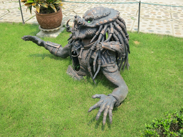 A Predator statue leaps out of the grass on the grounds of the White Temple.