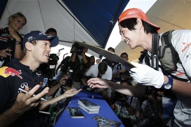 Себастьян Феттель и болельщик McLaren смеются на автограф-сессии Гран-при Японии 2011
