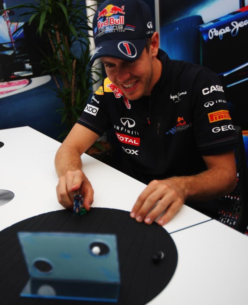 Себастьян Феттель играет в игрушку во время интервью на Гран-при Японии 2011
