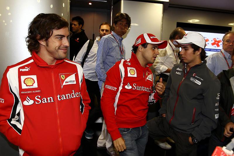 улыбающийся Фернандо Алонсо наблюдает за разговором Фелипе Массы и Серхио Переса на Гран-при Венгрии 2011