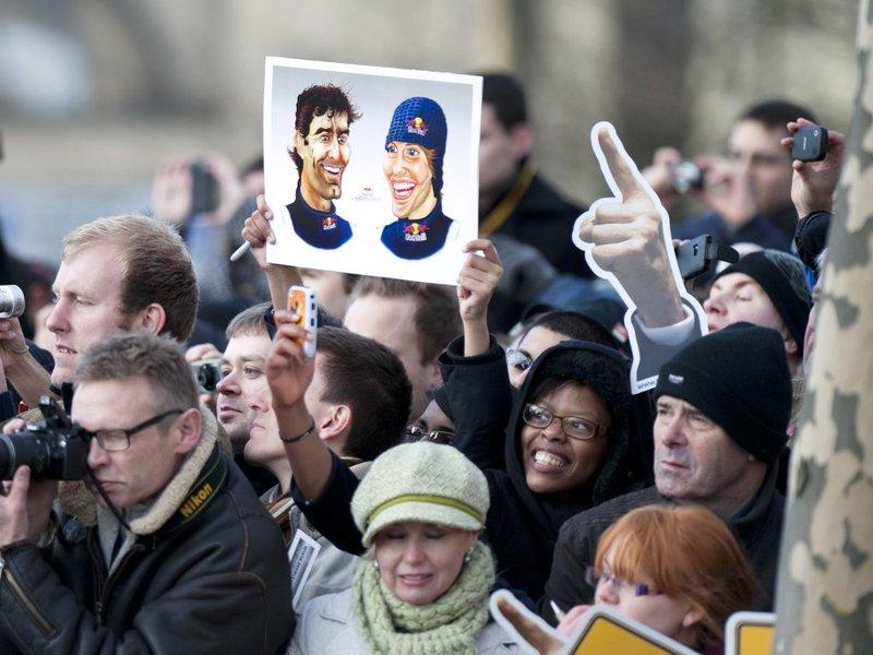 болельщик держит в руках карикатуры Марка Уэббера и Себастьяна Феттеля в Милтон-Кинс 10 декабря 2011