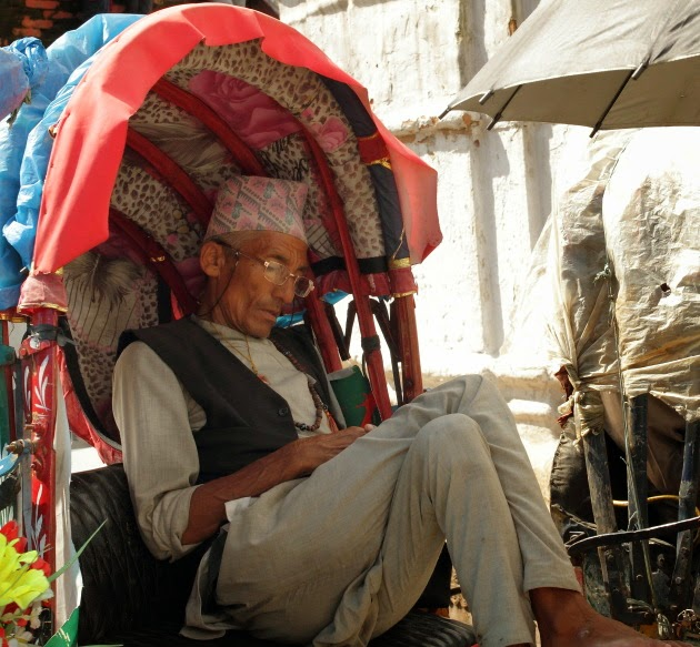 Nepali gentleman sleeping in a cycle rickshaw