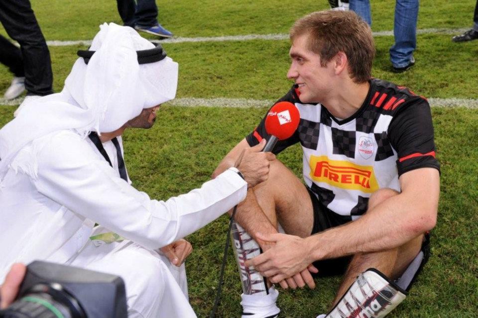 Виталий Петров дает интервью на футбольном матче на Гран-при Абу-Даби 2011
