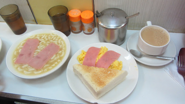 The set breakfast menu: macaroni soup (with ham), scrambled eggs, toast with butter, and coffee/tea.