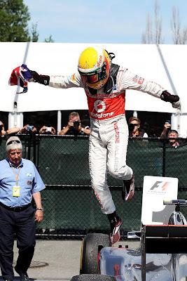 Льюис Хэмилтон выпрыгивает из своего McLaren с британским флагом в руке после победы на Гран-при Канады 2012