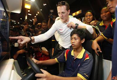 Михаэль Шумахер дает советы мальчику на гоночном симуляторе на Гран-при Малайзии 2012