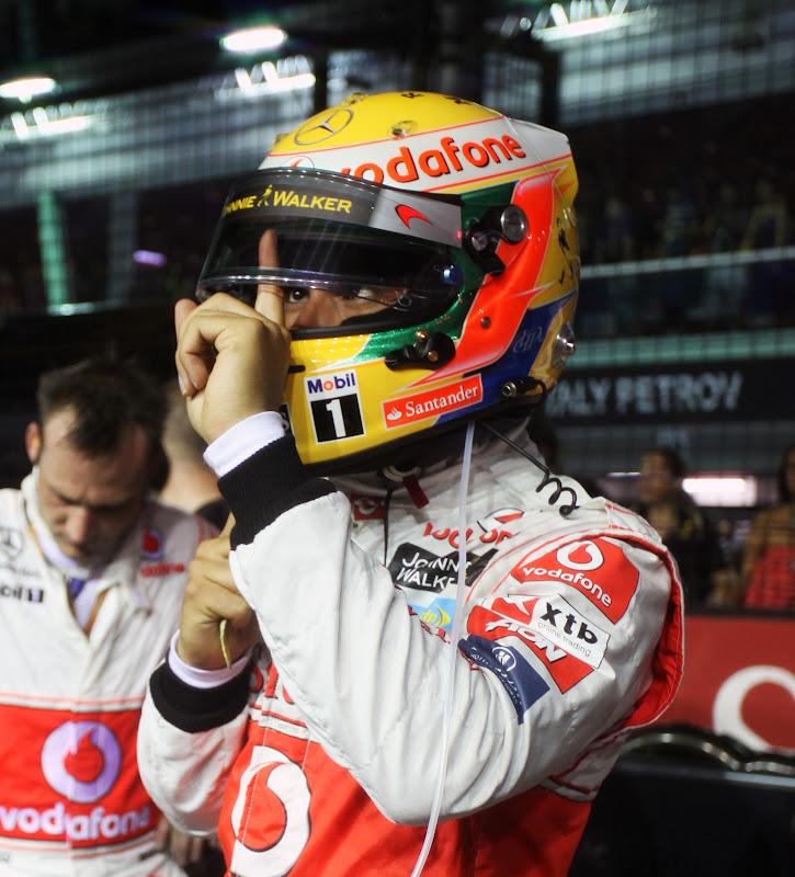 Льюис Хэмилтон протирает визор пальцем перед стартом гонки на Гран-при Сингапура 2011