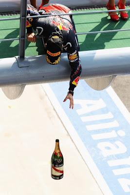 Себастьян Феттель бросает бутылку шампанского с подиума на Гран-при Италии 2011
