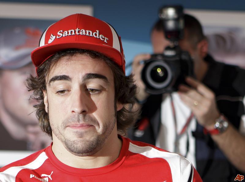 уставший Фернандо Алонсо и фотограф позади на автограф-сессии Гран-при Абу-Даби 2011