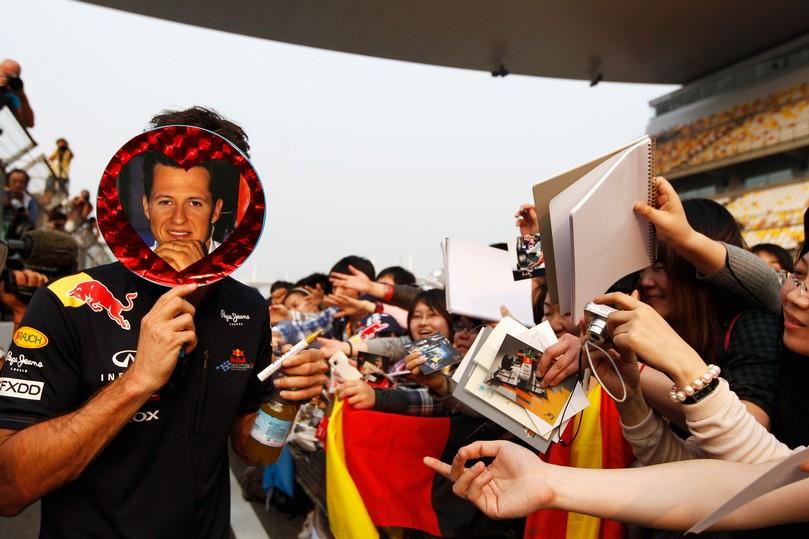 Марк Уэббер закрывается кругом Михаэля Шумахера на раздаче автографов для болельщиков Шанхая на Гран-при Китая 2011
