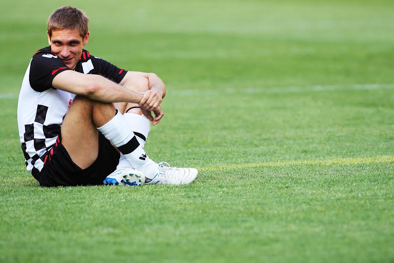 Виталий Петров сидит на футбольном поле Монте-Карло на Гран-при Монако 2011