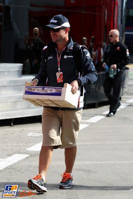 Рубенс Баррикелло несет ящик по паддоку на Гран-при Испании 2011