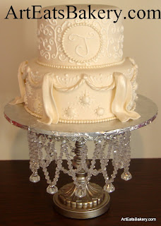 Two tier ivory fondant wedding cake design with white royal icing curlicues, edible pearls, starbursts, swags and drapes
