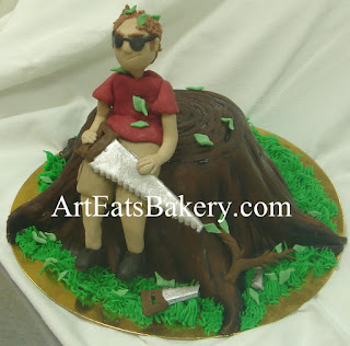 Edible sugar figure man sitting on tree stump birthday cake with saw, tree branches and broken saw