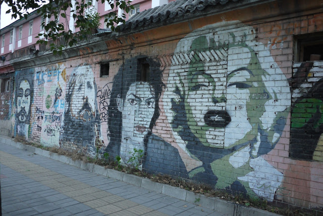 portraits of Michael Jackson and Marilyn Monroe on a brick wall
