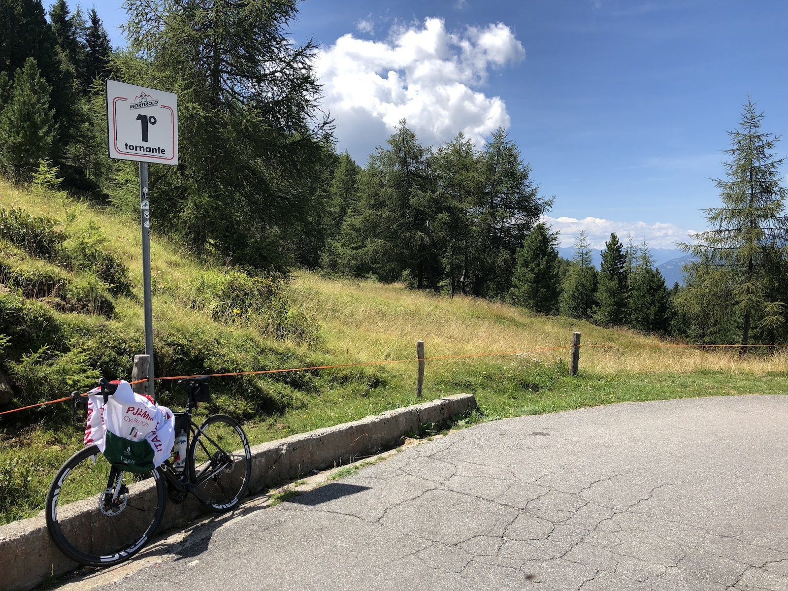 Climbing Passo del Mortirolo from Grossio - tornanti 1 sign (hairpin) with bike leaning against it.