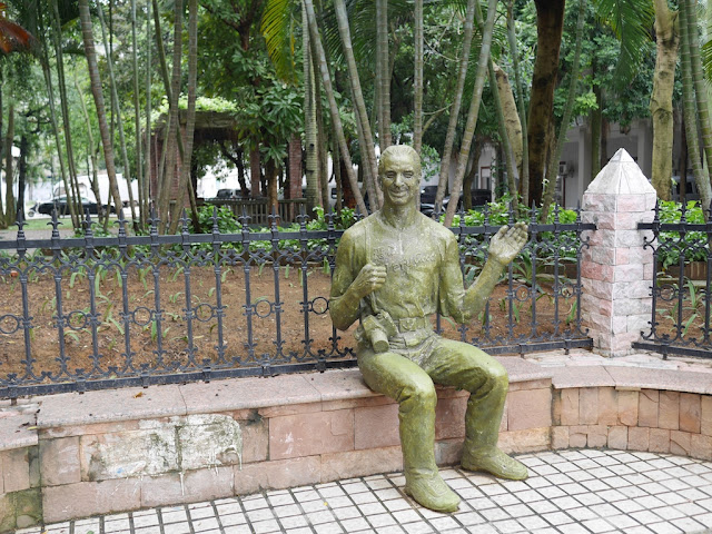 "statue of Western-looking man with a camera and wearing a shirt with the words ""湛江 Very Good"""